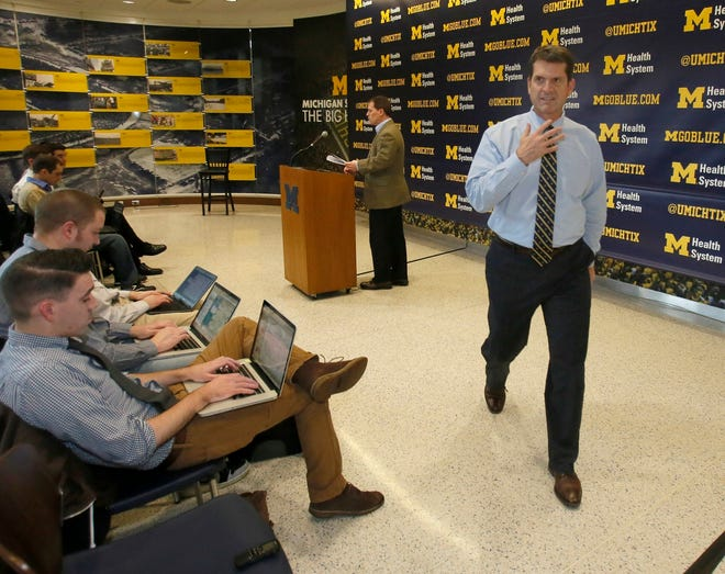 Michigan coach Jim Harpo turns away after completing his first signature day press conference in Michigan at the Chembeciller Hall on Wednesday February 4, 2015.