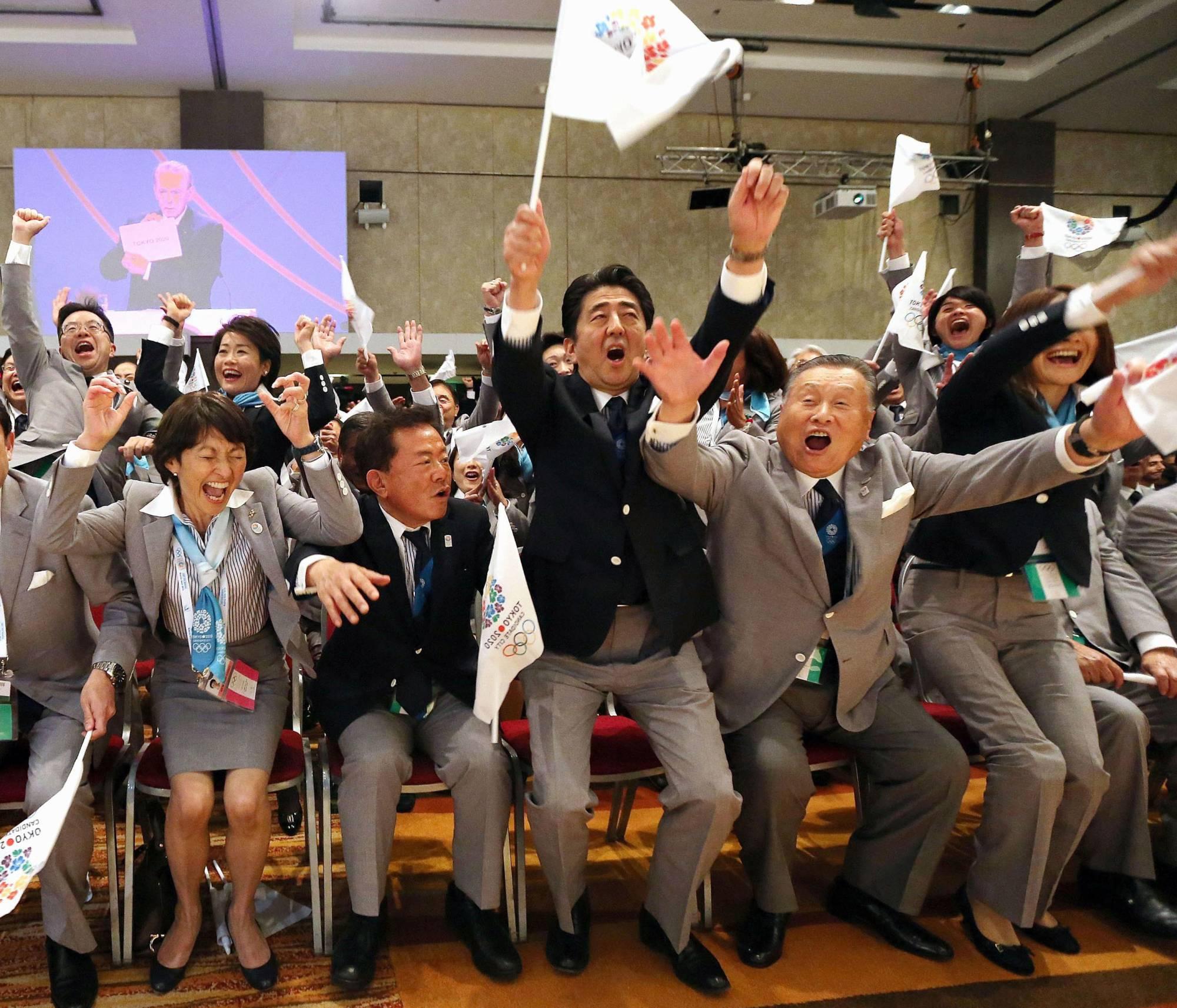 Бывший премьер-министр Ёсиро Мори (второй справа) празднует в Буэнос-Айресе праздник после того, как Токио был выбран в качестве города-организатора летних Олимпийских игр 2020 года в сентябре 2013 года.  Киодо